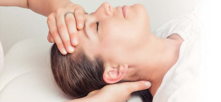 Frau lässt ihren Kopf entspannt und mit geschlossenen Augen in den Händen einer anderen Frau ruhen.