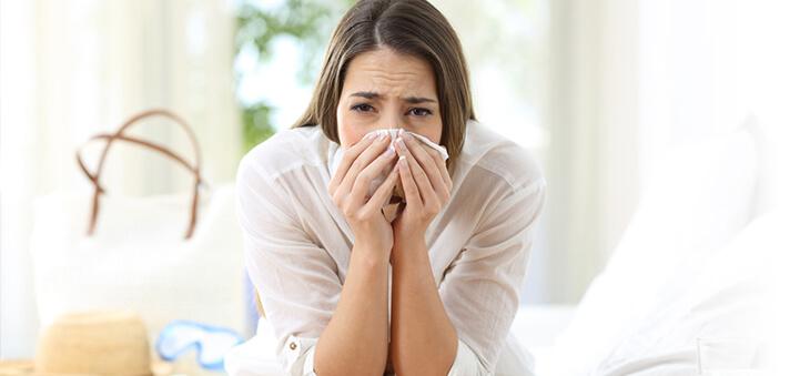 Frau niest in ein Taschentuch.