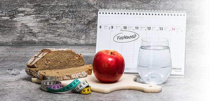 """Brot, Apfel, Wasserglas und Maßband liegen vor einem Kalender, auf dem """"Fastenzeit"""" steht."""