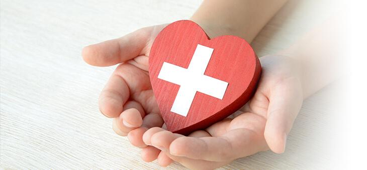 Hände halten rotes Herz aus Holz mit weißem Kreuz darauf.