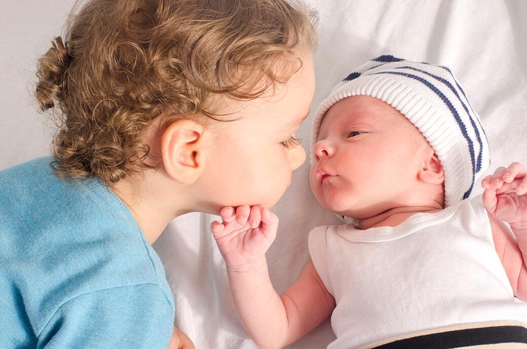 Kleinkind und Baby blicken einander an.