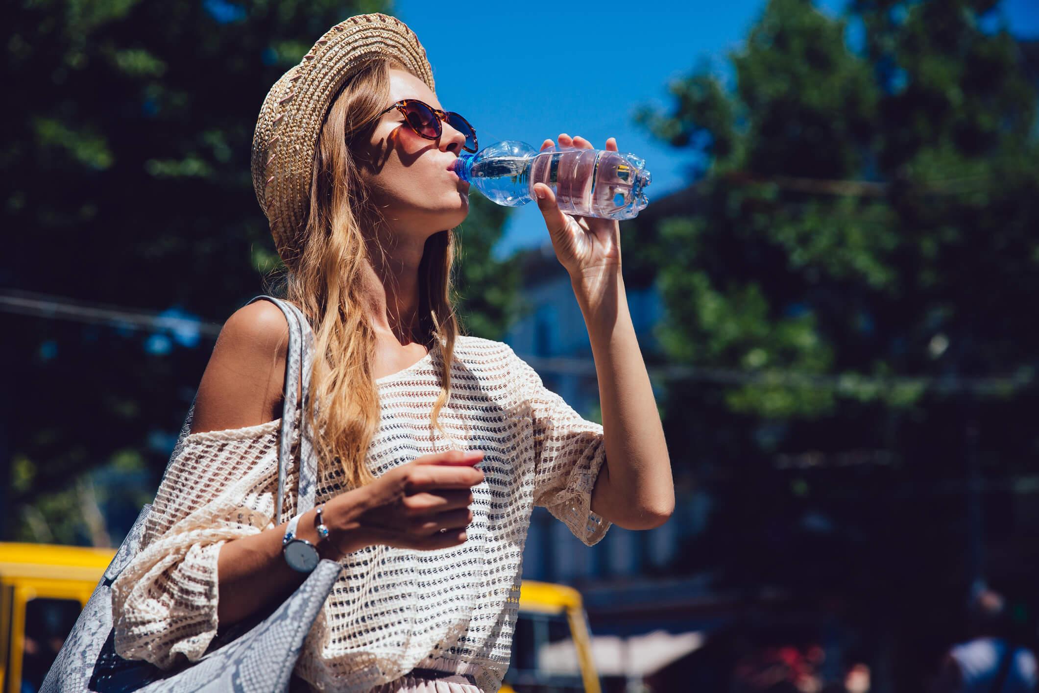 Frau mit Strohhut und Sonnenbrille trinkt aus Wasserflasche.