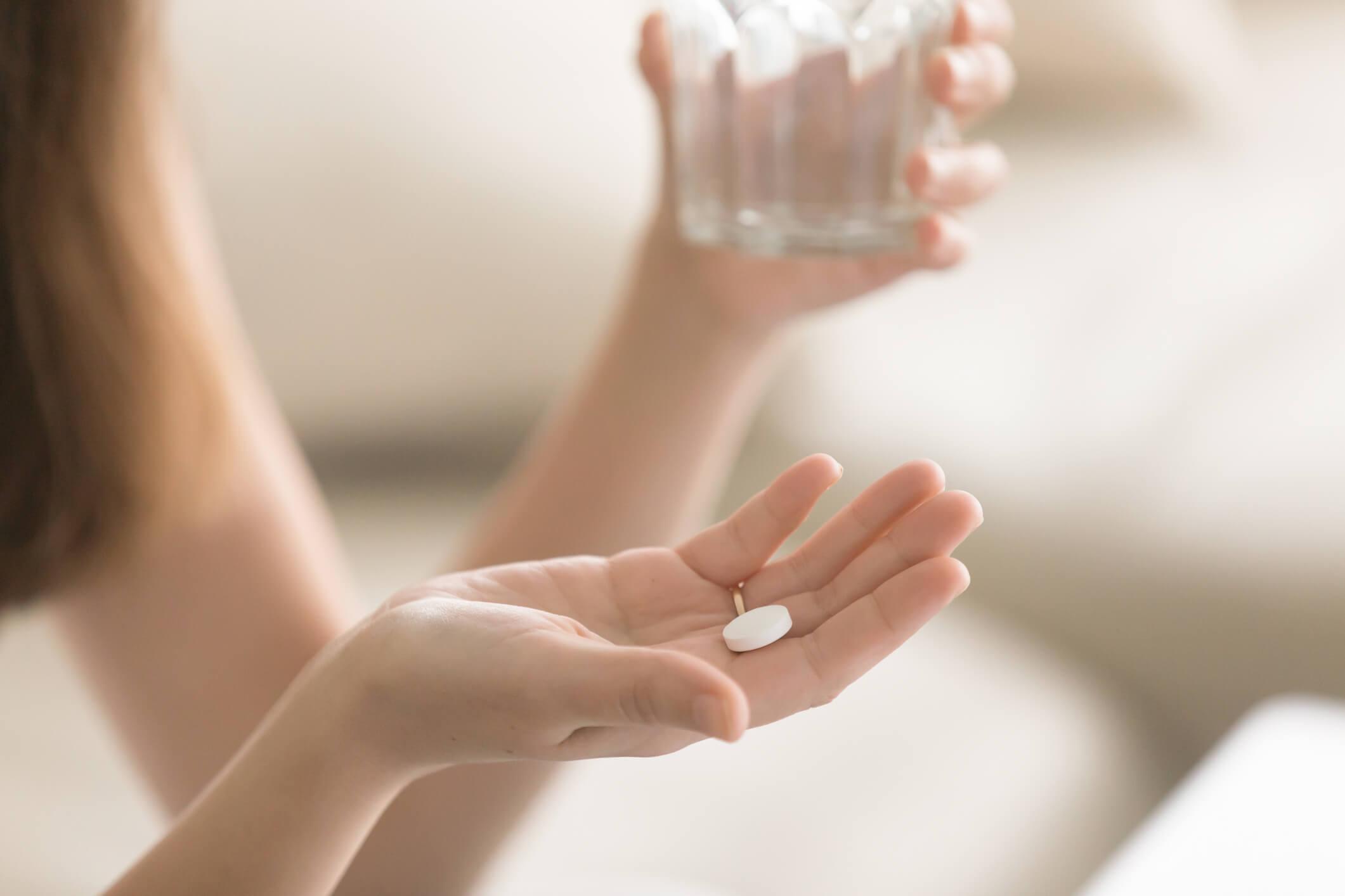 Frau hält Wasserglas in der einen und Tablette in der anderen Hand.
