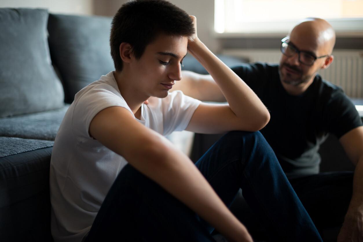 Teenager sitzt vor dem Sofa während ein Mann Trost spendet.