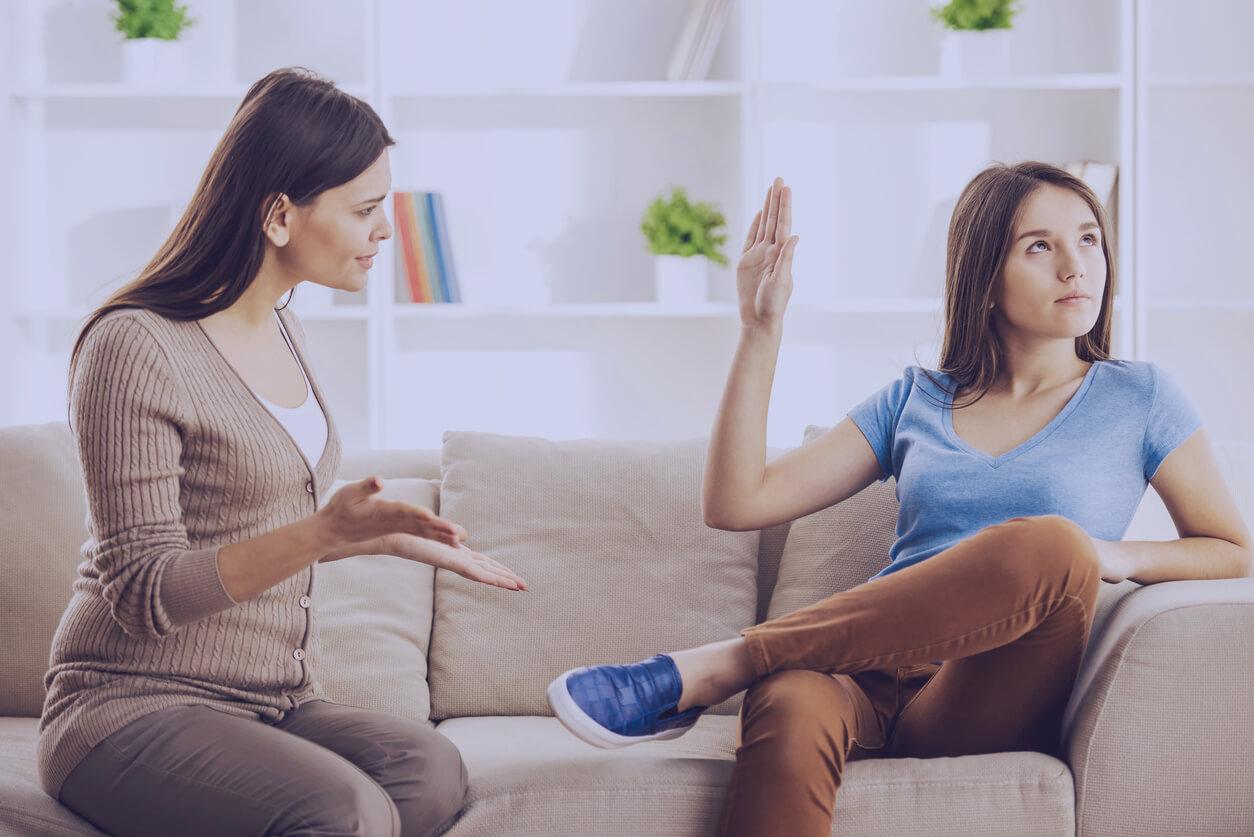 Frau diskutiert mit Jugendlicher, die abwehrend die Hand hebt.