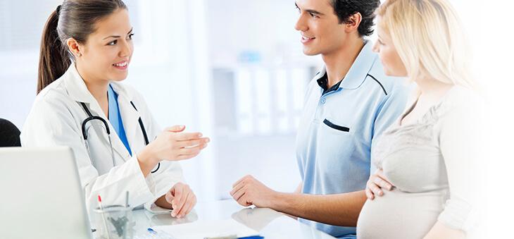 Schwangere Frau und Partner sprechen mit Ärztin.