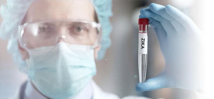 """Probengläschen mit der Aufschrift """"ZIKA"""" in Arzthänden."""