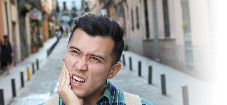Mann verzieht das Gesicht er leidet unter Zaehneknirschen bzw. Bruxismus
