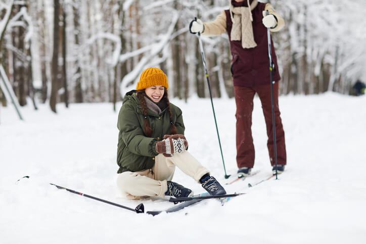 Frau-mit-Skiern-Knieverletzung