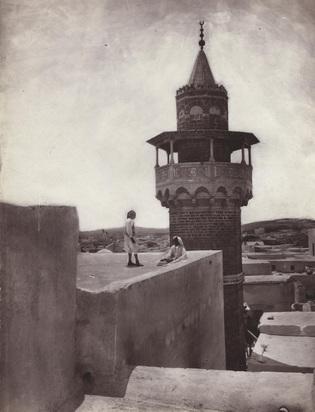 Gloeden Wilhelm von, Tunis, zwei Männer auf dem Hausdach vor Minarett, 1890er Jahre