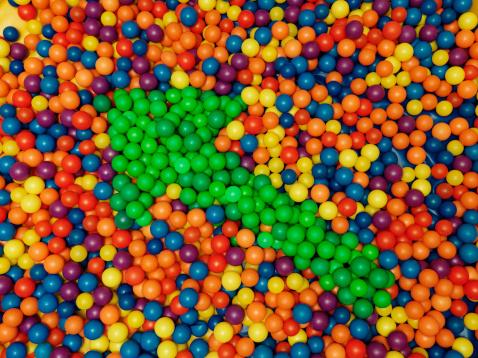 Green arrow shape in an abundance of balls