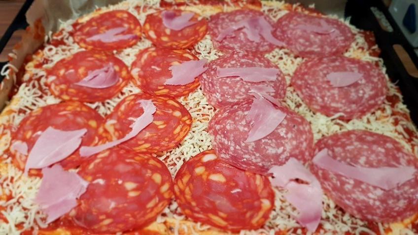 den-Pizzaboden-mit-Tomatensoße-und-Wurst-belegen