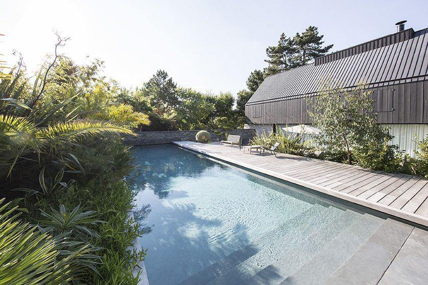 Belle piscine avec plage de terrasse en bois et joliment entourée de végétation