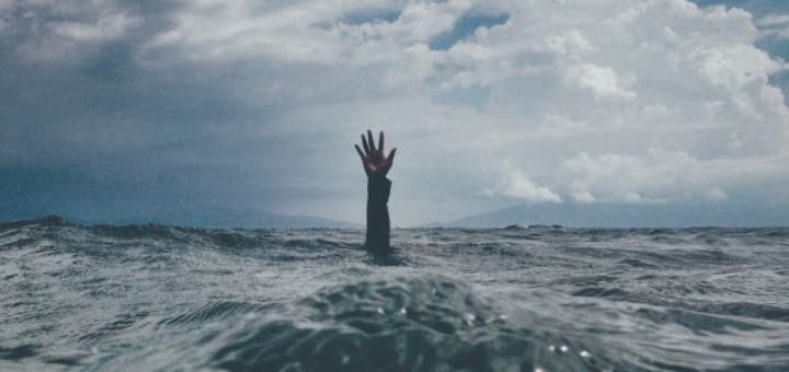 a hand reaching out of the ocean