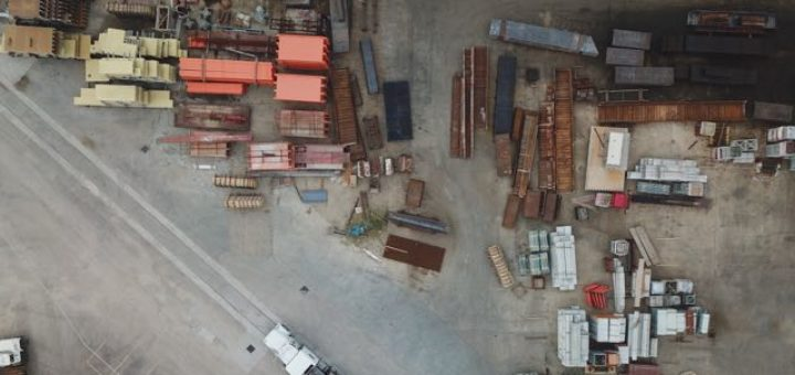 industrial construction site with trucks and shipping containers