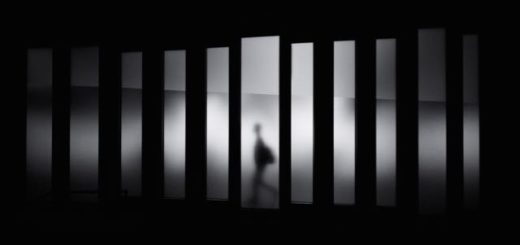 abstract man walking behind a tinted glass wall