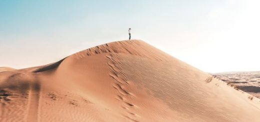 woman standing at the top of a sand dune