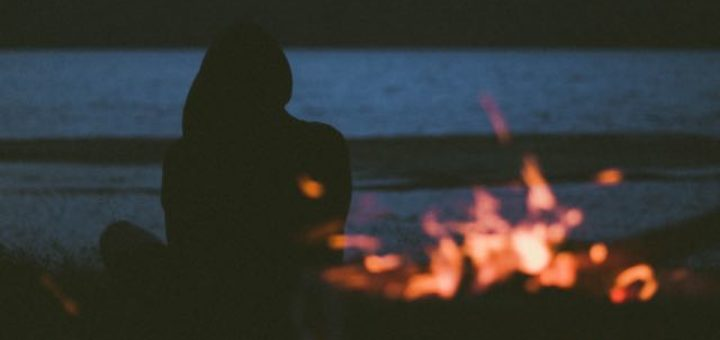 a person in a hoody sitting by the fire near a lake