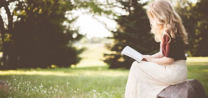 a blond girl in white dress reading a book in the park