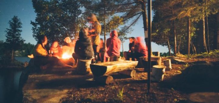 group of friends by a lake around a bonfire