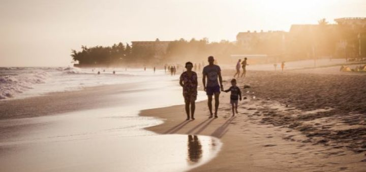 family of three walking on the beach at sunset