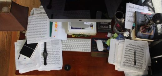 a desk with computer crowded with sheet music