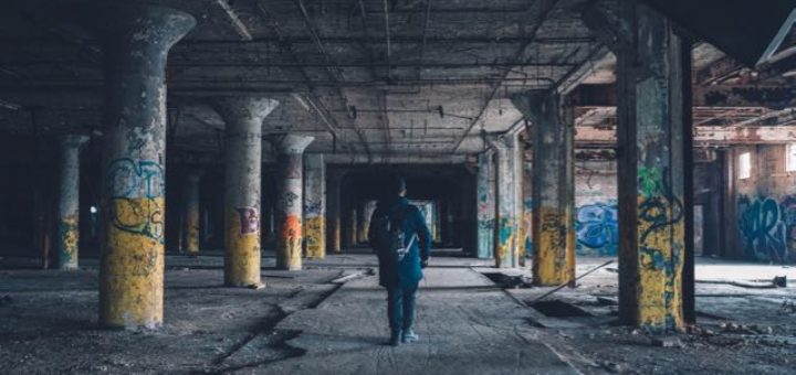 man walking in abandoned graffiti building