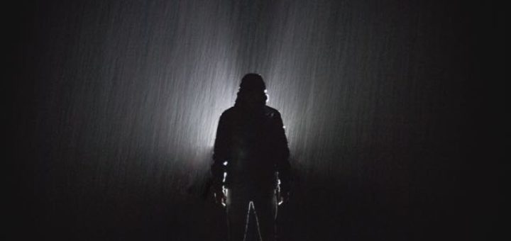 man standing in the rain at night