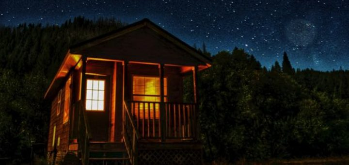cottage in the forest with starry night sky