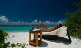 En kvinna solar och njuter på stranden på en resa till Maldiverna