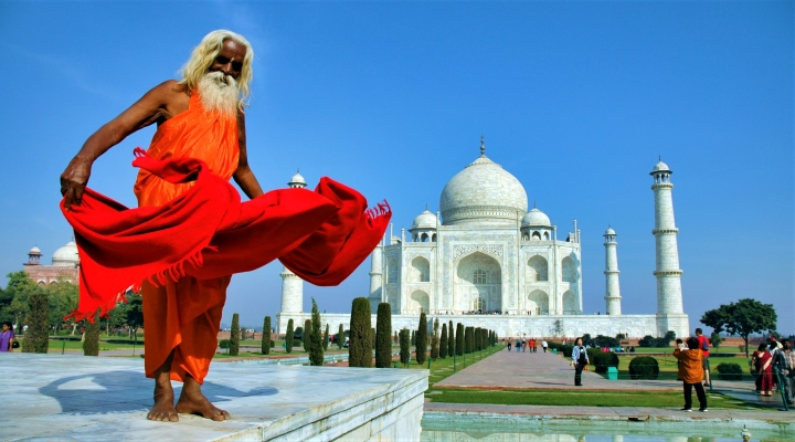 En man poserar framför Taj Mahal på en resa till Indien