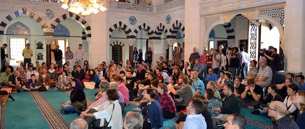 Ein Tag der offenen Moschee in Deutschland. Viele Personen sitzen sich auf dem boden, um mehr über die Moscheen zu lernen