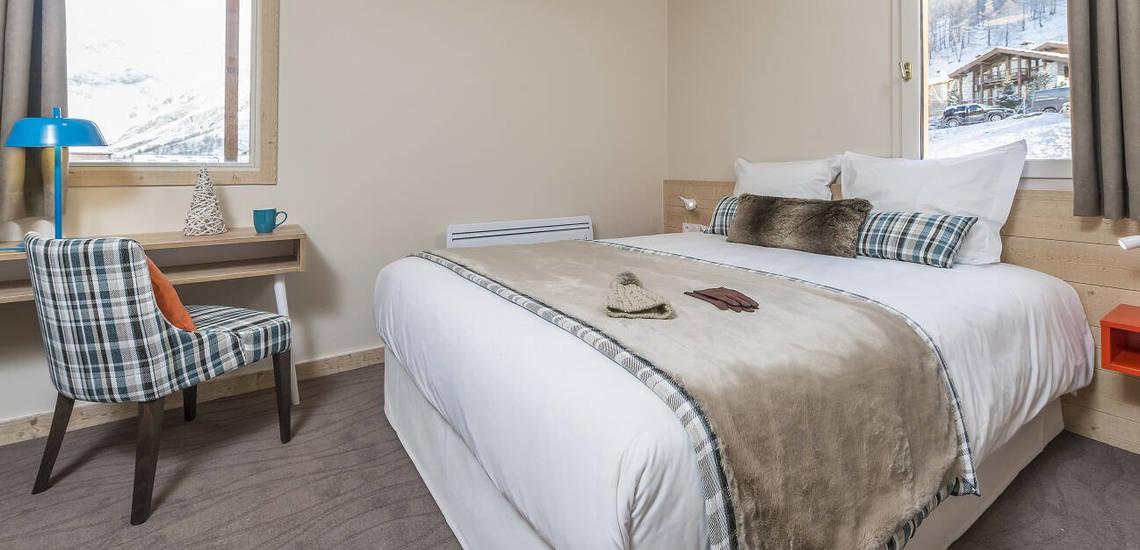 Schlafzimmer mit Doppelbett in einer Ferienwohnung der Residenz Les Chalets du Jardin Alpin in Val d'Isere