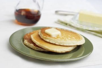 Drie stuks roomkaas pannenkoeken met klontje boter en siroop.