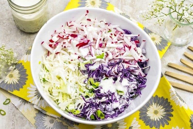 Bord met een kleurrijke koolsalade met dressing.