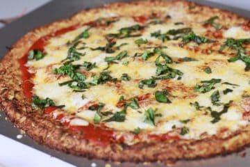 Een heerlijke koolhydraatarme bloemkoolpizza belegd met tomatensaus en mozzarella.