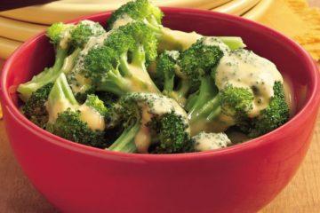 Portie gekookte broccoli met gesmolten kaas.