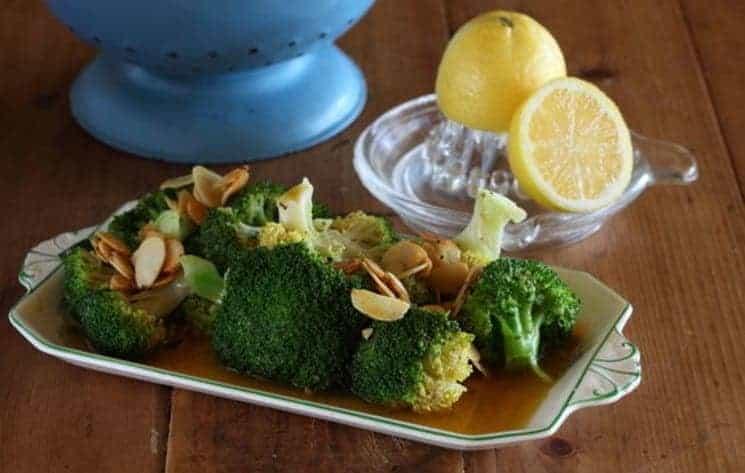 Een portie broccoli in amandel-citroen boter gegarneerd met geschaafde amandelen.