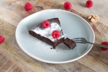 Puntje koolhydraatarme chocolade taart gegarneerd met verse frambozen en Steviala frost.