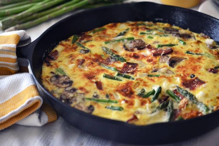 Koekenpan met gebakken frittata met asperges en champignons.