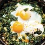Een pan vol met gebakken eieren met spinazie, prei, lente-ui en een saus van yoghurt en knoflook.