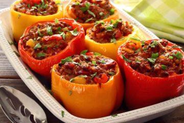 Ovenschaal met zes gevulde paprika's met chorizo en ei.