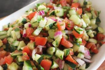 Schaal met Israëlische salade bestaande uit komkommers, tomaat, rode ui en kruiden.