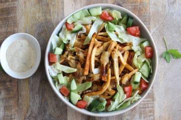 Heerlijk portie kapsalon met pastinaak frietjes, shoarma, sla, tomaat, komkommer en knoflooksaus.