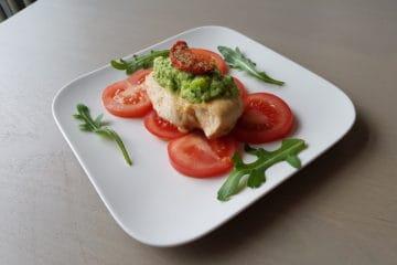 Portie kipfilet met plakjes tomaat en courgettesaus gegarneerd met zongedroogde tomaat en rucola.
