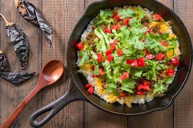 Heerlijke pan met bloemkoolrijst en taco gekruid vlees, ijsbergsla en tomaat.