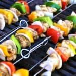 Stokjes souvlaki met rode en gele paprika en rode ui op de grill.