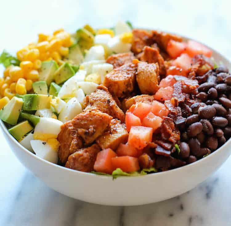Schaal met heerlijke salade gemaakt van kip, bonen, tomaat, kip, avocado en dressing.