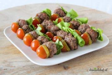 Heerlijke koolhydraatarme prikker met tomaat, augurk, sla en een mini hamburger.