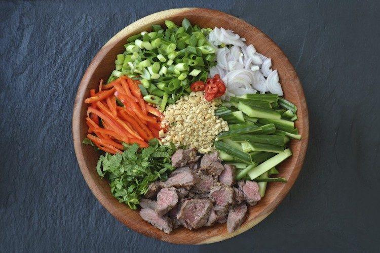 Thaise biefstuksalade met groente en dressing.